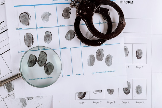 Police handcuffs and criminal fingerprints card, with magnifying glass, top view Premium Photo