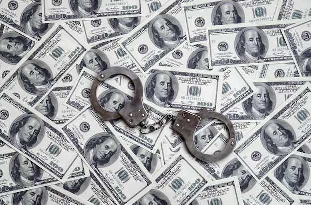 Police handcuffs lie on a lot of dollar bills. Premium Photo