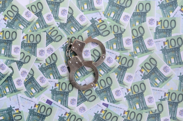 Police handcuffs lies on a set of green monetary denominations of 100 euros. Premium Photo
