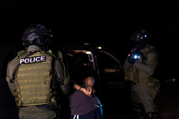 A police intervention unit arrests illegal immigrants at hostels. Premium Photo
