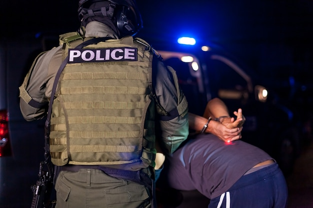 A police officer puts handcuffs on a criminal's hands during an arrest. police car with flashing lighthouses. copy space Premium Photo