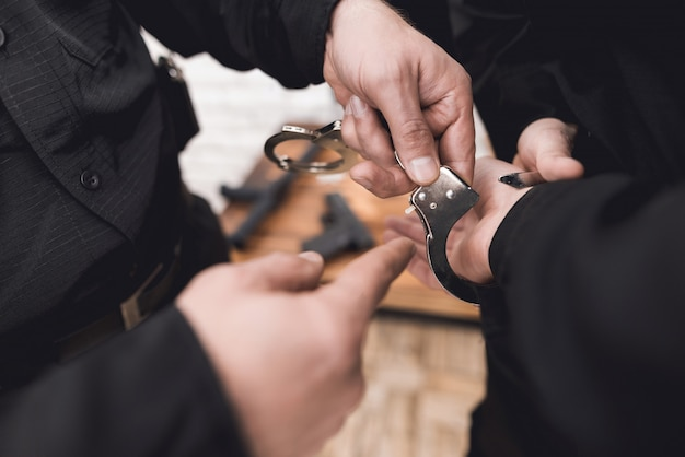 Police officer shows subordinates how to use a handcuffs. Premium Photo