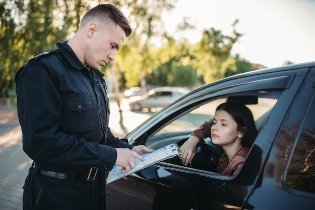 制服を着た警官が女性ドライバーに元気に書いている Premium写真