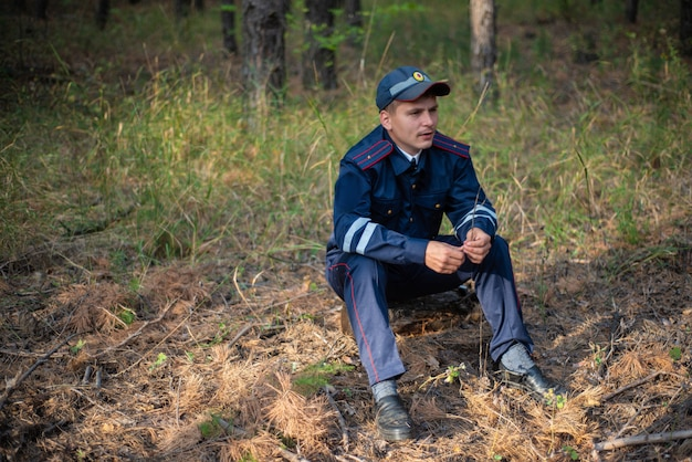 Policeman sits on the grass in the forest and thinks Premium Photo