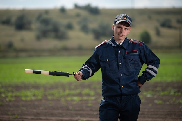 Policeman in uniform with a rod in his hand Premium Photo