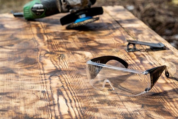 Polished wood grinder abrasive wheel and safety glasses. free text, copy space, Premium Photo