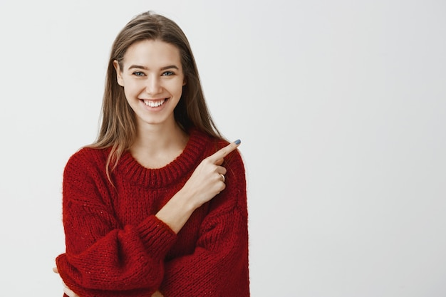 Вежливый дружелюбный продавец, готовый помочь найти дорогу. портрет привлекательной радостной европейской женщины в красном свободном свитере, указывающий на правый верхний угол, широко улыбающийся и выражающий позитивное настроение Бесплатные Фотографии