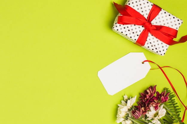 Polka dot wrapped gift box with blank tag and flower bunch on green backdrop Free Photo