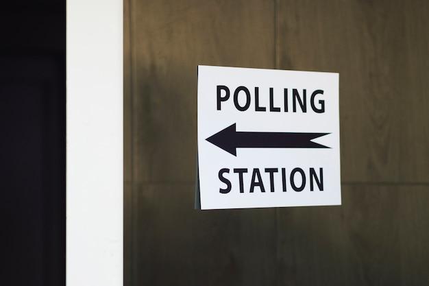Знак избирательного участка с направлением на деревянной стене Бесплатные Фотографии