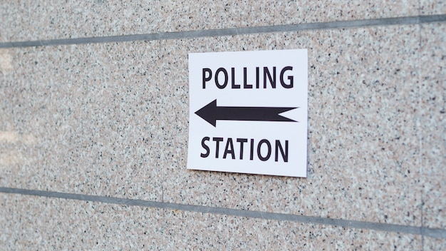 Polling station sign with direction on wall Free Photo