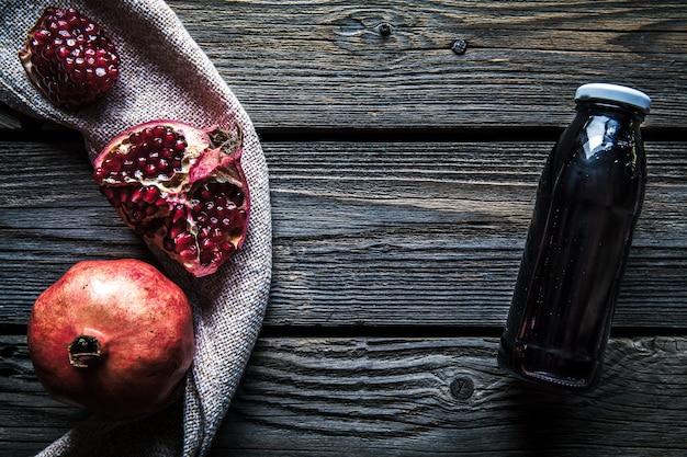 Гранат и бутылки эссенции или настойки на деревянном деревенском столе Premium Фотографии