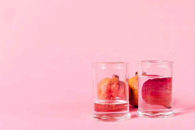 Pomegranate behind glasses with water Free Photo