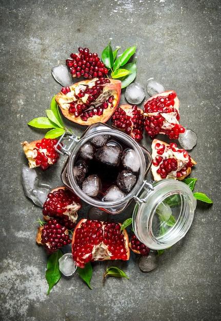 Гранатовый сок в жестяной банке со льдом и дольками с листьями. на каменном столе. вид сверху Premium Фотографии