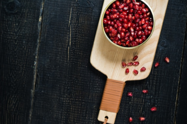 Pomegranate kernels in a bowl on a wooden cutting board. Premium Photo