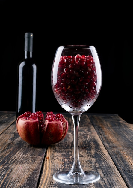 Pomegranate wine pomegranate in wine glass on wooden table Free Photo