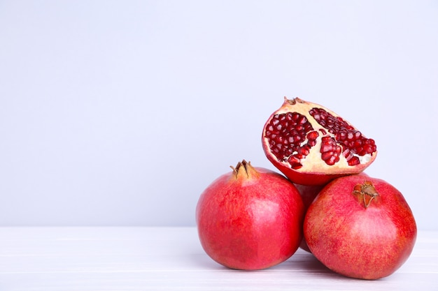 Pomegranates and half of ripe pomegranate on a grey background Premium Photo