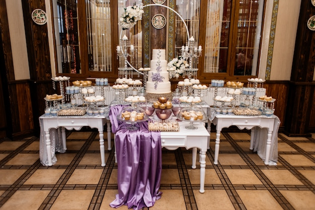 Pompous wedding candy bar and decorated with lavender wedding cake Free Photo