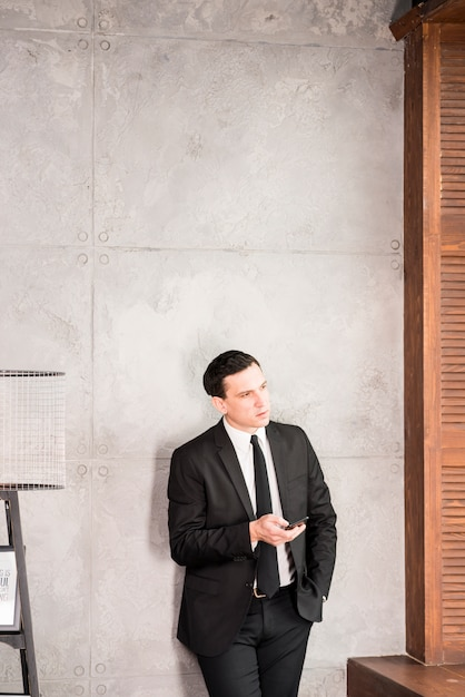 Pondering handsome businessman with smartphone looking away Free Photo