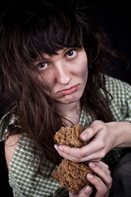 Poor beggar woman with a piece of bread. Premium Photo