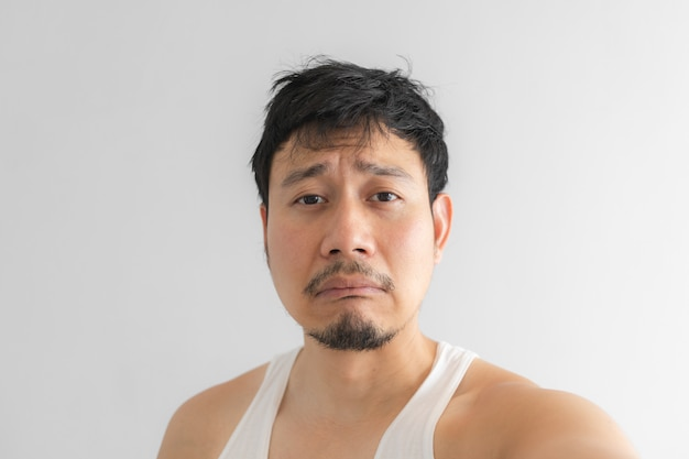 Poor and depressed face of man on grey background. concept of desperate life. Premium Photo