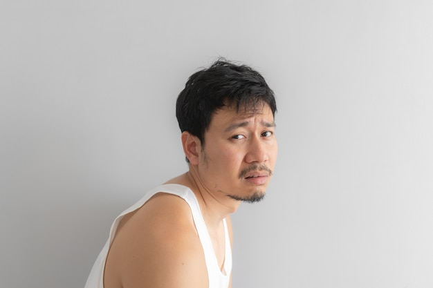 Poor and depressed man wear white tank top on grey background. concept of desperate life. Premium Photo