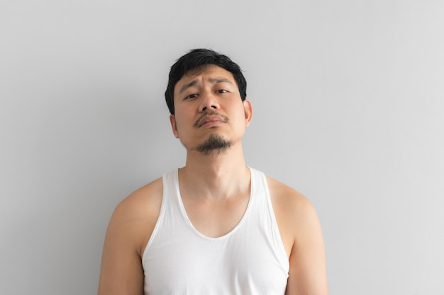 Poor and depressed man wear white tank top on grey background. Premium Photo