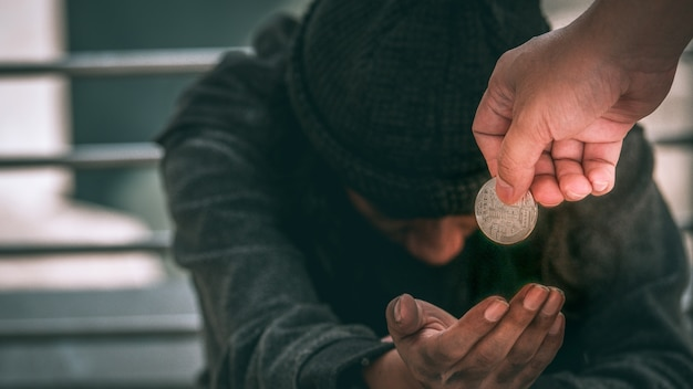 Poor homeless man or refugee sitting on on the dirty floor recieving money. Premium Photo