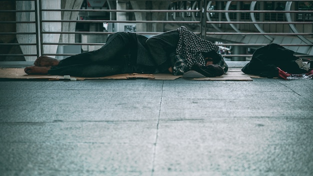 Poor homeless man or refugee sleeping on the floor of public path way in the city Premium Photo