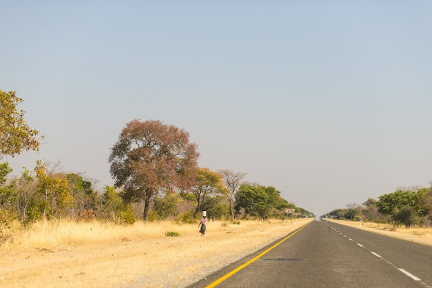 Poor woman walking on the roadside in the rural caprivi strip, the most populated region in namibia, africa. Premium Photo