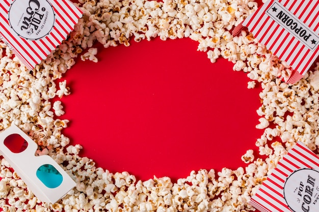 Popcorn and 3d glasses with copy space for writing the text on red backdrop Free Photo