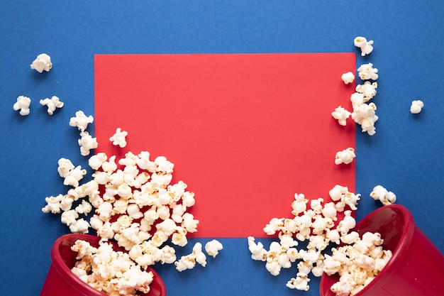 Popcorn on blue background and red empty card Free Photo