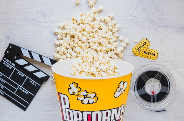 Popcorn bucket and filmstrip on table Free Photo