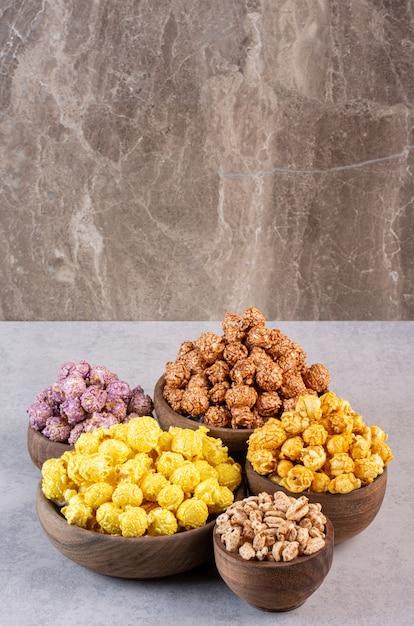 Caramelle e fiocchi di popcorn ammucchiati in ciotole su marmo. Foto Gratuite