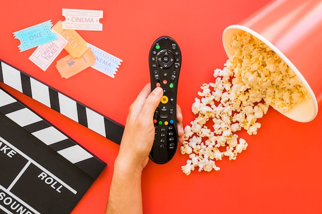 Popcorn, clapperboard and hand holding remote control Free Photo
