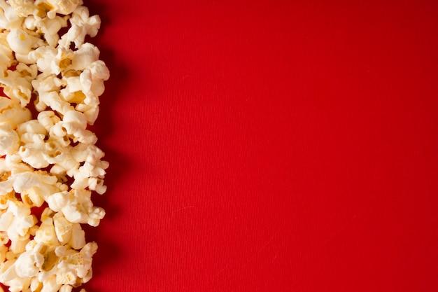 Попкорн композиция на красном фоне с копией пространства Premium Фотографии