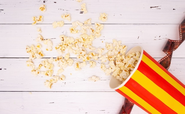 Popcorn, film on a white wooden background, top view. the concept of cinema. Premium Photo