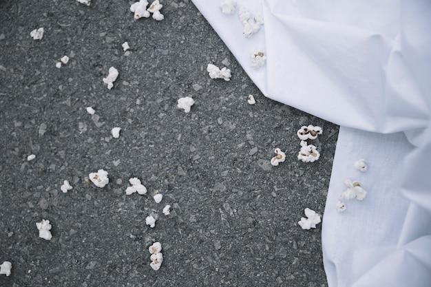 Popcorn on ground near white sheet Free Photo