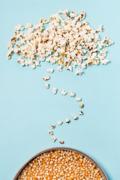 Popcorn over the popcorn seeds against blue background Free Photo