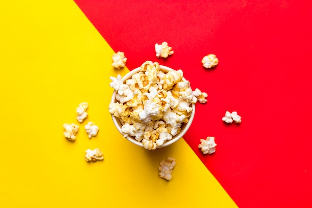 Popcorn in a red and white cardboard box on a red and yellow Premium Photo