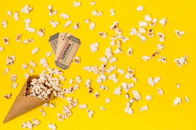 Popcorns spilled from the waffle cone with cinema ticket Free Photo
