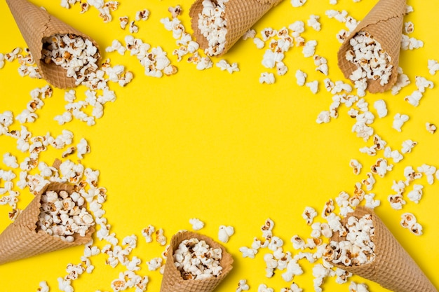 Popcorns with waffle cones on yellow background with space for writing the text Free Photo