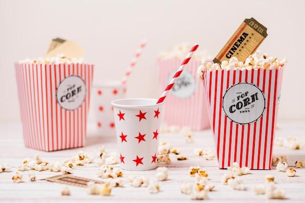 飲むガラスとわら木製テーブルの上のpopcornsボックスの映画館のチケット 無料写真