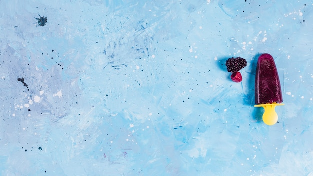 Popsicle and berries on blue background Free Photo