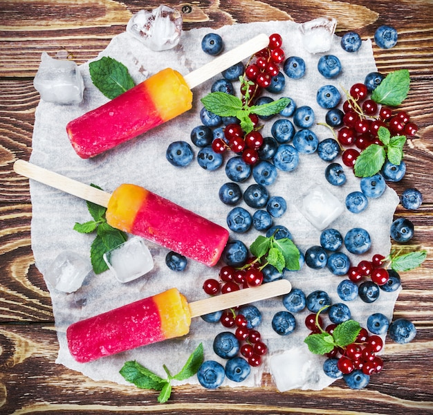 Popsicles with red currants and blueberries on a wooden Premium Photo