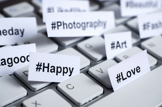Popular hashtags printed on white paper inserted into the keyboard. Premium Photo