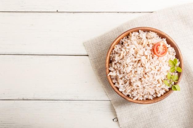 白い木製の背景に木製のボウルに玄米のおpor Premium写真