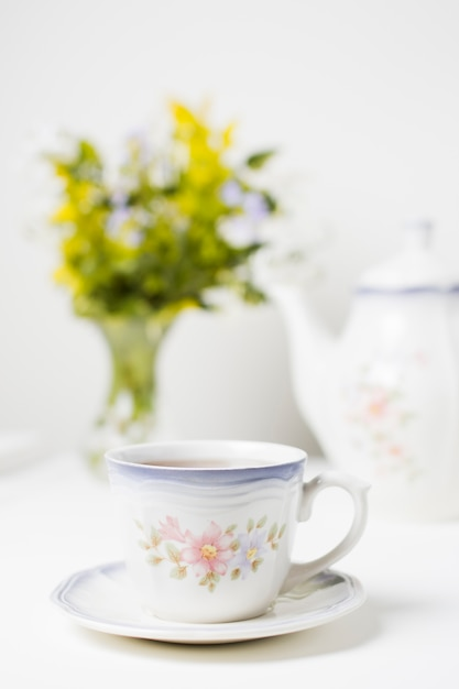 Porcelain cup of tea and saucer on white table against selective background Free Photo