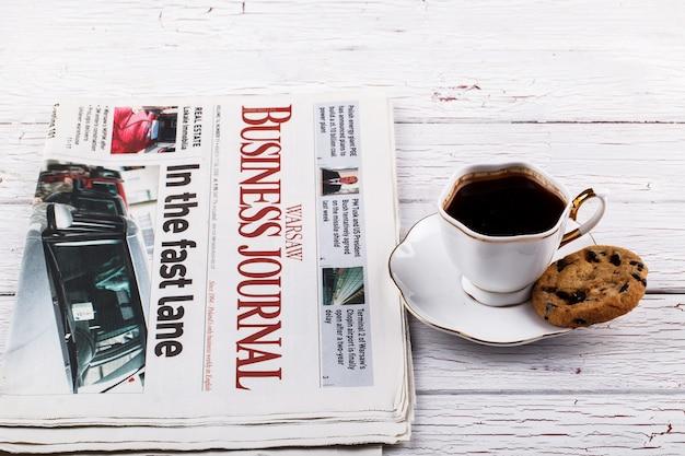 Cangkir porselen dengan kedai kopi di depan surat kabar dan buku Foto Gratis