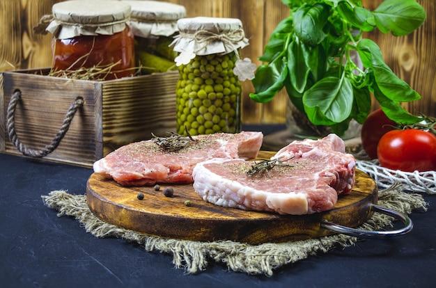 Отбивные из филе свинины на разделочной деревянной доске. Premium Фотографии