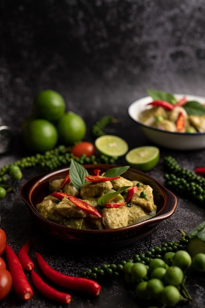 Pork green curry in a brown bowl with spices on a black cement background Free Photo